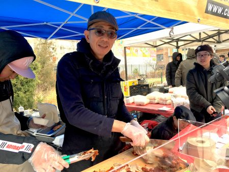 老闆葉先生正在把烤鴨肉一片片切成薄薄的。這是他們第二年擺攤了,生意依舊火爆。