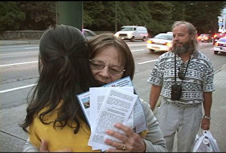 图:温哥华中领馆前,爱德华姐弟与法轮功学员拥抱,表示支持。(大纪元图片)