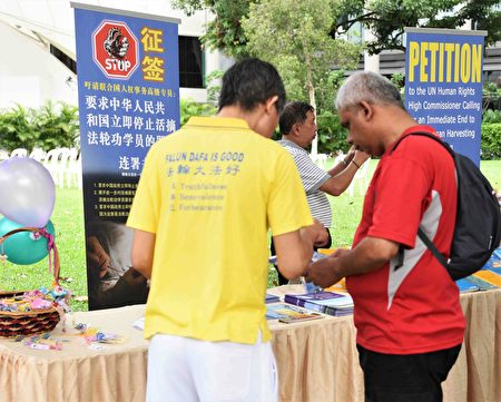 法輪功學員向過路的民眾講述真相。不少民眾在反活摘征簽表上簽名。(蘇每善/大紀元)