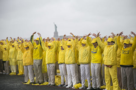 """2017年5月13日,法轮大法弟子在纽约总督岛(Governors Island)举行大型排字活动,排出""""法正乾坤""""。图为在雨中排字的法轮功学员在炼法轮功的第二套功法---法轮桩法(大纪元)"""