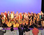 """5月22日,在北卡凯瑞艺术中心上演了""""从故乡的心弦响起""""音乐会。图为演出结束后,凯瑞市政界友人、台湾侨界人士与乐团演员合影留恋。(程志毅/大纪元)"""