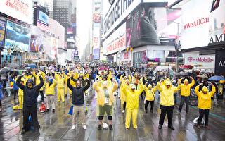 来自全球各地的部分法轮功学员为庆祝法轮大法洪传25周年,聚集纽约举行各项庆祝活动。图为2017年5月13日,纽约时代广场雨中集体炼功。(季媛/大纪元)