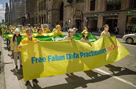 2017年5月12日,剛從大陸來到美國的法輪功學員趙虎(左一)參加慶賀法輪大法洪傳25周年和第18屆「世界法輪大法日」紐約曼哈頓大遊行。(謝東延/大紀元)