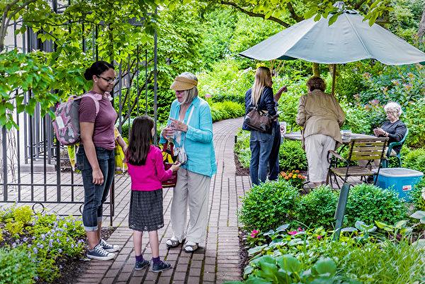 杰斐逊市场花园的白发义工们与游客交流。(张静怡/大纪元)