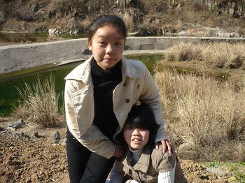 2017年5月12日被非法抓捕的北京法轮功学员蒋立宇(站立者)和姊姊蒋炼娇。(明慧网)