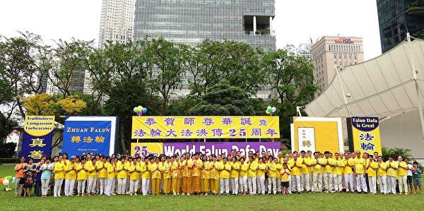 二零一七年五月二日,新加坡法轮功学员在芳邻公园庆祝即将来临的世界法轮大法日。图为学员们集体合影,虔敬合十,恭祝师尊生日快乐。(明慧网)