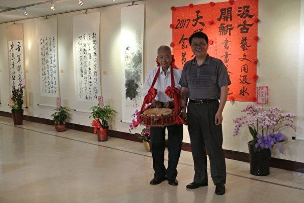 天臘書畫會聯展茶會,會長吳政安的父親(87歲),到場獨秀擊鼓祝賀。(周美晴/大紀元)