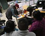 人们在移民办公室签署文件。(John Moore/Getty Images)