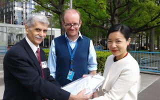 波多黎各法輪功學員Mark Casilieris(左一)和聯合國副秘書長的代表Li Fung(右一)。 (Tatiana Casilieris提供)