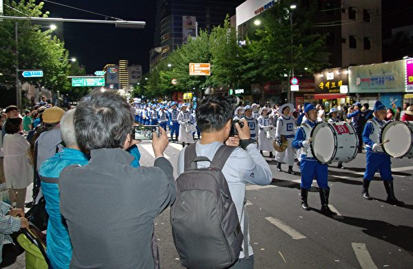 很多市民拿手机争相拍照行进中的天国乐团。(金国焕/大纪元)