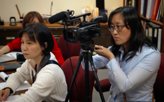 本報記者蔡溶和新唐人記者安心在2015年報導國寶銀行案。 (《國寶——小可入獄》截圖)