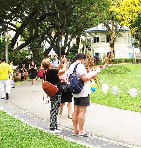路過的游客被慶典活動所吸引,駐足觀看並拍照留念。(Tony /大紀元)