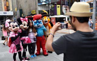 时代广场处处可以见到与游客拍照的卡通乞丐。 (Stan Honda/AFP/Getty Images)