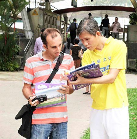 法輪功學員向過路的民眾講述真相。不少民眾在反活摘征簽表上簽名。(Tony /大紀元)