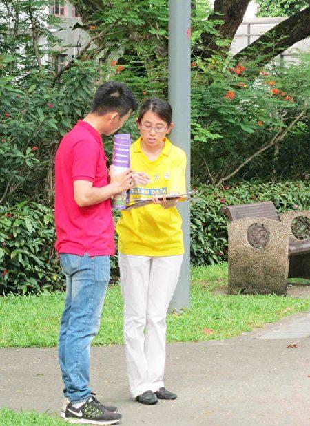 法輪功學員向過路的民眾講述真相。不少民眾在反活摘征簽表上簽名。(王秀/大紀元)