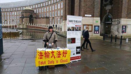 英国法轮功学员碧琪·詹姆士(Becky James)女士在市政厅前向往来的行人讲述自己修炼法轮功得到的益处。(照片由本人提供)