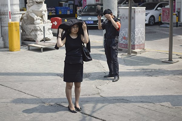 A woman shelters under an her cloth against the strong sun as she stands next to a security guard who takes off his hat along a street in Beijing on May 18, 2017.  Beijing weather department issues an yellow warning signal for heat wave on May 16 with temperatures soaring near 35 degrees Celsius (95F) in the coming days. / AFP PHOTO / WANG ZHAO        (Photo credit should read WANG ZHAO/AFP/Getty Images)
