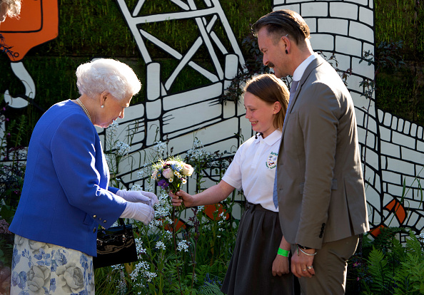 LONDON, ENGLAND - MAY 22: Queen Elizabeth II is presented with a posy by Caitlyn James a Y6 from Swansea during her visit to the RHS Chelsea Flower Show press day at Royal Hospital Chelsea on May 22, 2017 in London, England. The prestigious Chelsea Flower Show, held annually since 1913 in the Royal Hospital Chelsea grounds, is open to the public from the 23rd to the 27th of May, 2017. (Photo by Julian Simmonds - WPA Pool / Getty Images)