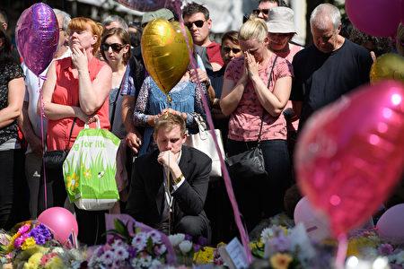 图:5月22日晚英国曼彻斯特体育场发生自杀炸弹恐怖袭击,导致22人死亡、59人受伤。图为5月25日为遇难者默哀的曼彻斯特市的民众。(Leon Neal / Getty Images)