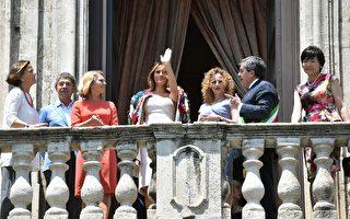 G7峰會領導人的配偶在卡塔尼亞市政廳的陽台上向民眾致意。從左至右:意大利總理保羅·甘蒂洛尼的妻子伊曼紐拉·毛羅(Emanuela Mauro), 德國總理默克爾的丈夫約阿希姆·薩爾(Joachim Sauer),歐洲理事會主席唐納德·圖斯克的妻子瑪格麗塔·圖斯克(Malgorzata Tusk),美國第一夫人梅莉妮亞·川普(Melania Trump), 卡塔尼亞市長的妻子Amanda Succi, 卡塔尼亞市長Enzo Bianco,日本首相安倍晉三的妻子安倍昭惠(Akie Abe)。(GIOVANNI ISOLINO/AFP/Getty Images)