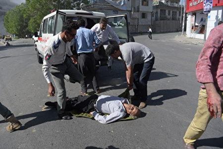 5月31日阿富汗首都喀布尔发生大爆炸事件,人们在救助伤者。 (SHAH MARAI/AFP/Getty Images)