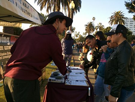 Albert Roman周末至圣莫妮卡海滩与往来游客讲述法轮功学员在中国大陆的遭遇。(徐绣惠/大纪元)