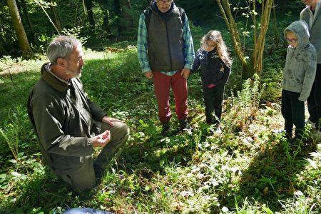 环境专家伯乐伊(Yann Breull)为参观者讲解泥土的结构和作用。(林丽霞/大纪元)
