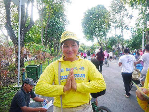 印尼巴厘島當地法輪功學員。因這位女法輪功學員剛剛介紹過法輪功真相,旁邊的民眾認真地看起真相傳單。(蕭律生/大紀元)