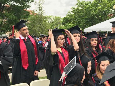 畢業生在學位帽上撥穗,象徵他們的人生翻開新的一頁。