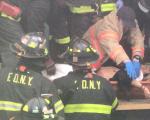 被撞男子被消防员和警察抬上7号线103街-可乐娜广场站月台。 (李红/大纪元)
