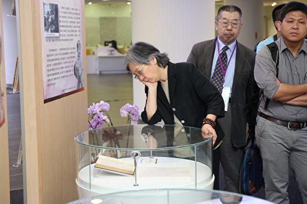 唐文标遗孀邱守榕教授低头看先生的手稿。(清华大学提供)