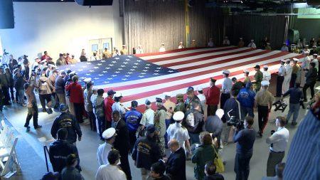 图为近百名海军战士和老兵们一起展开了100英尺长的美国国旗。 (安心/大纪元)