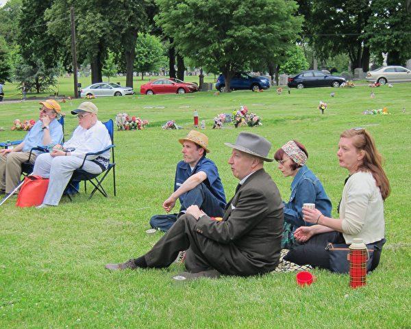 坐在草地上观看音乐会的民众。(大纪元)