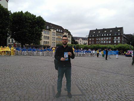 游行队伍到达城堡广场,举行集会演讲。刚到德国才几个月的27岁Hermin一直关注活动。他表示迫害很不好,反迫害活动应该一直举办,祝愿中国好运。(祝兰/大纪元)
