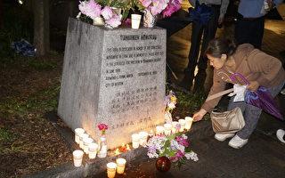 """参加波士顿六四悼念会的一位女士,将点燃的蜡烛放在华埠牌坊公园旁的""""天安门纪念碑""""前,以烛光寄思,向当年的民主斗士致敬。(廖述祥/大纪元)"""