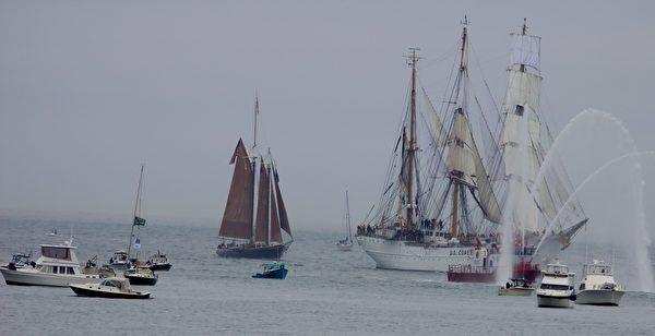 领航的高桅船出现了,这是来自美国海岸护卫队的老鹰号,旁边两艘消防水船,对其喷出高高的水柱表示欢迎。(SCOTT PHILLIPS/大纪元)