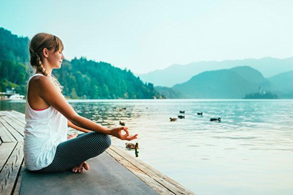 冥想。年轻女子在湖边沉思。(Fotolia)