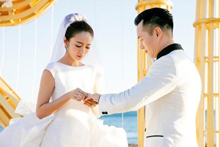 在200位亲友的见证下,安以轩(左)与新郎交换婚戒。(安以轩工作室提供)
