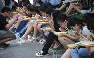 中國青少年近視率世界第一,而且呈現出低齡化。圖為濟南市的研究生在大會堂外進餐。(VCG/VCG via Getty Images)