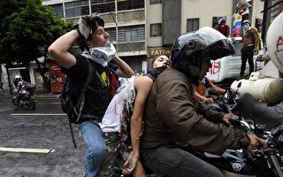 委内瑞拉1名青少年7日在抗议总统马杜洛政府的新一波活动中丧命。图为一名看似无意识的抗议者(中)被同伴带走。(JUAN BARRETO/AFP/Getty Images)