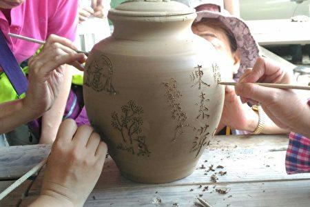 團員在陳雄鎮老師傅完成的手拉坯作品上簽名留念。(廖素貞/大紀元)