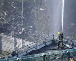6月14日凌晨,倫敦24層的格倫費爾大廈發生大火,整棟公寓樓完全被大火吞噬。圖為消防員疲於滅火。(Leon Neal/Getty Images)