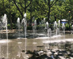 炎熱的夏日裡,圓形的花崗岩噴水池是孩子們的最愛。(楊帆/大紀元)