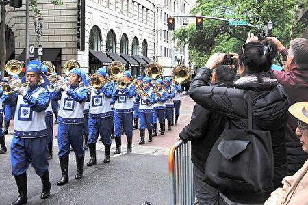 """天国乐团在""""玫瑰节大巡游""""一路演奏《法轮大法好》、《凯旋》、《神圣的歌》等原创乐曲,宏伟而平和的乐曲把法轮大法的美好带给了这座美丽的城市。(明慧网)"""