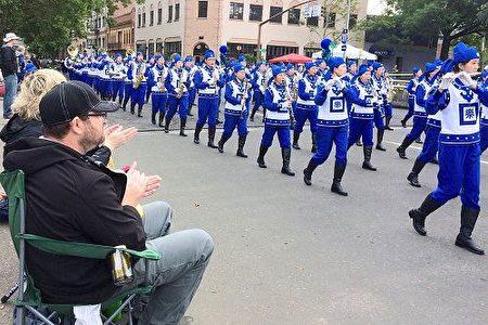 """天国乐团在""""玫瑰节大巡游""""中一路演奏《法轮大法好》、《凯旋》、《神圣的歌》等原创乐曲,宏伟而平和的乐曲把法轮大法的美好带给了这座美丽的城市。(明慧网)"""