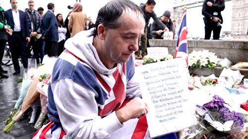 一位身披英国国旗的先生蹲在鲜花边,一边为罹难者祈祷,一边举着自己写的悼念词,长时间在淅沥细雨中坚守着。(任真/大纪元)