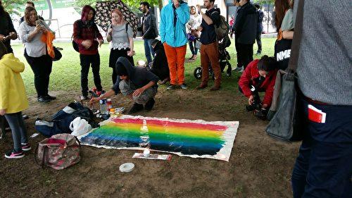 一位居住在伦敦的白人小伙子做了一幅彩虹画,表达对和平的向往。(夏松/大纪元)