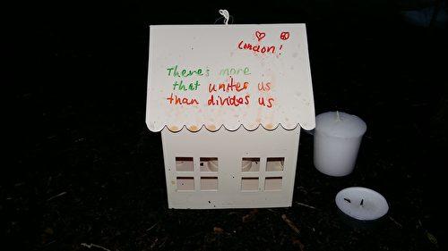 """一位女士做了一个白色小屋,里面放着蜡烛,屋顶一面写着:""""伦敦永远强大。""""另外一面写着:""""将我们团结在一起的力量比分裂我们的力量更强大。""""(夏松/大纪元)"""