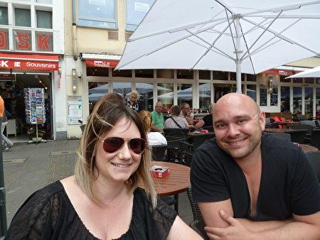 Patrick Fleckenstein(右)和Caroline Frank坐在老市场的咖啡馆里,全程听了法轮功集会上的发言。(文婧/大纪元)