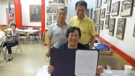 中华公所义工钱英收到石婆婆送来的感谢信,开心与她的先生章德利(左后)与同事。